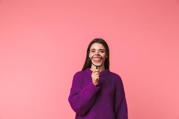 돋보기를 통해 찾고 핑크 이상 격리 서 스웨터를 입고 재미 어린 소녀 미소 프리미엄 사진