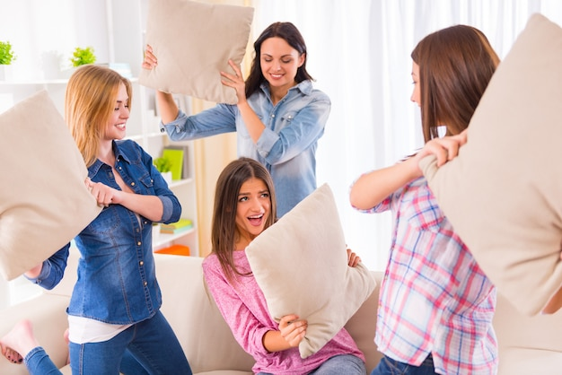 Funny young girls pillow fight on the sofa. Premium Photo