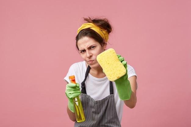 カジュアルな服、エプロン、保護ゴムの手袋を着用し、清潔感に取りつかれたおかしい若い主婦。 無料写真