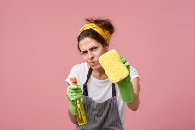 Funny young housewife wearing casual clothes, apron and protective rubber gloves obsessed with cleanliness, staring with measuring look while tidying up house until it's sparkly clean Free Photo