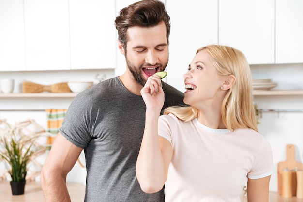 Funny young loving couple standing at kitchen and cooking Free Photo
