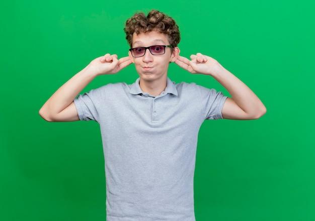 녹색 벽 위에 그의 귀를 Blowiong 뺨을 행복하고 쾌활한 서 보여주는 회색 폴로 셔츠를 입고 검은 안경에 재미 젊은 남자 무료 사진