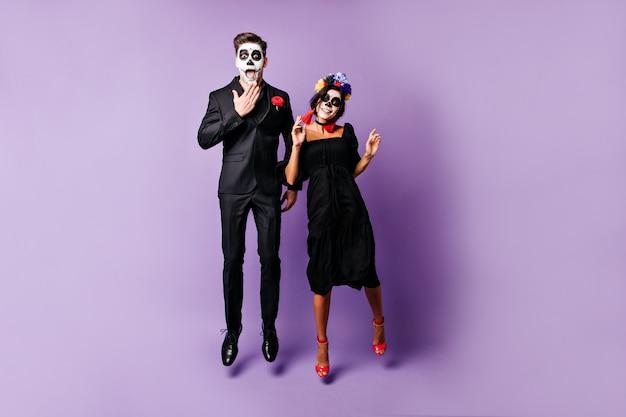 ハロウィーンのフェイスアートを持つ面白い若者は、紫色の背景にジャンプして、感情的にポーズします。 無料写真