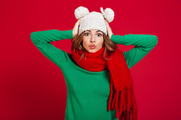 Funny young pretty lady wearing hat and warm scarf Free Photo