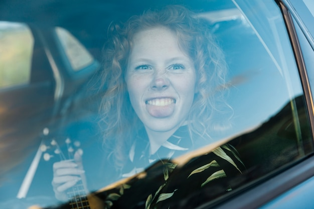 Funny young woman fooling around in car Free Photo