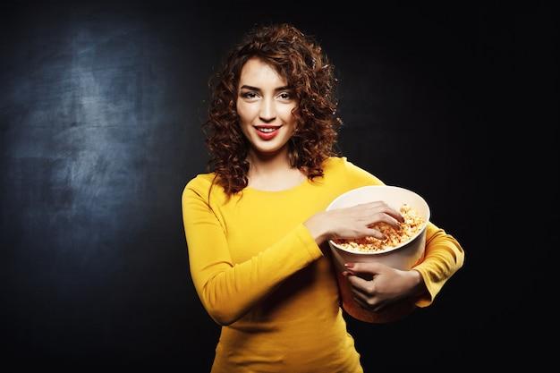 Giovane donna divertente che afferra manciata di popcorn con il sorriso allegro Foto Gratuite