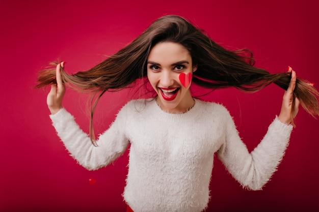 미소로 발렌타인 데이에 포즈를 취하는 솜털 스웨터에 재미 있은 젊은 여자 무료 사진
