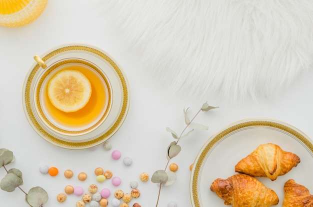 Fur; baked croissant; candies and ginger lemon tea cup on white background Free Photo