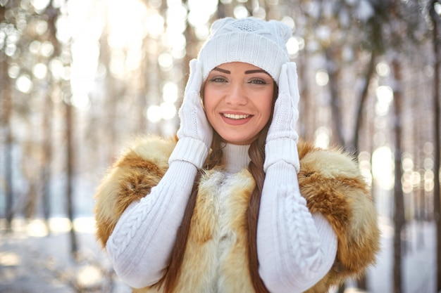 Fur vest on a beautiful young caucasian woman in a winter sunny forest Premium Photo
