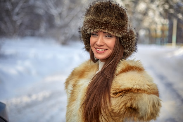Fur vest and winter hat on beautiful young caucasian woman in winter sunny forest Premium Photo