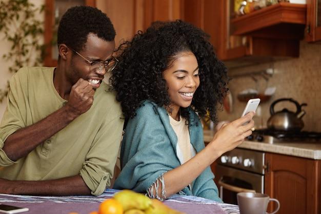 Разъяренный и ревнивый афроамериканец сжимает кулак в гневе и ярости, ловя его изменчивую подругу, когда она отправляет сообщение своему любовнику на мобильный телефон со счастливым и веселым выражением лица Бесплатные Фотографии
