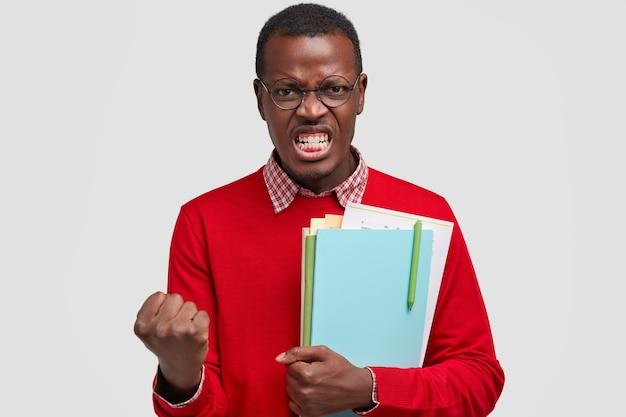 猛烈な黒ずんだ男は拳を握りしめ、白い歯を見せ、教科書を運び、何か悪いことに腹を立てる 無料写真