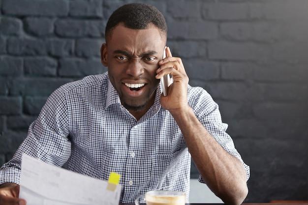 Giovane uomo d'affari afroamericano furioso e pazzo che grida al telefono astuto Foto Gratuite