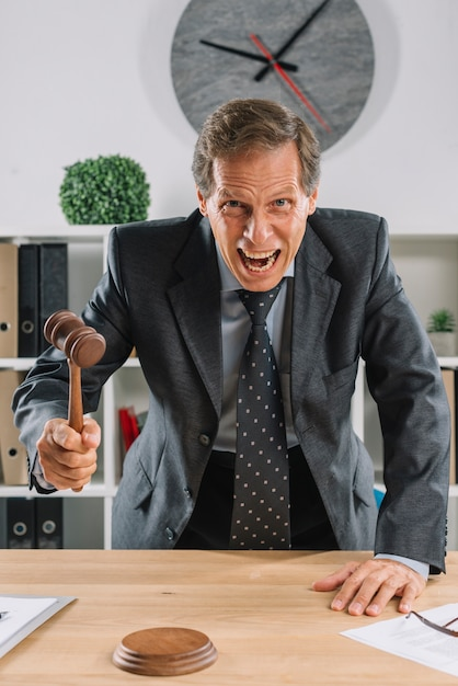 Furious mature lawyer giving verdict by hitting mallet at desk Free Photo