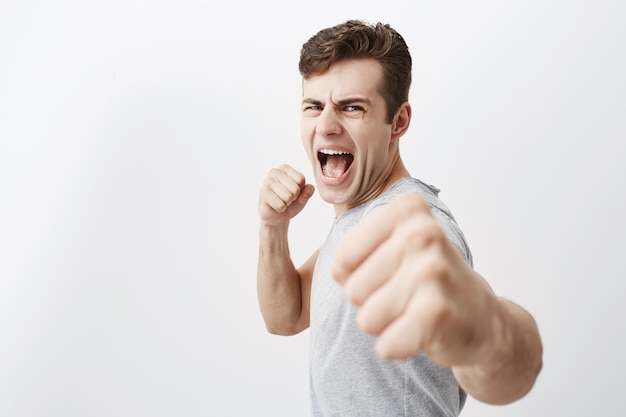 激怒した白人男性は怒りで叫び、顔をしかめ、拳を握り、犯罪者との戦いで身を守ります。絶望的なヨーロッパの男の黒い髪は彼の力を示し、拳を握り締めます。 無料写真