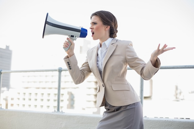 Furious stylish brown haired businesswoman shouting in a megaphone Premium Photo