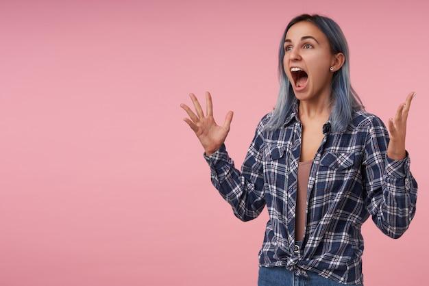 Furious giovane bella femmina con i capelli blu corti che solleva emotivamente le mani e tiene la bocca spalancata mentre urla con rabbia, isolato sul rosa Foto Gratuite