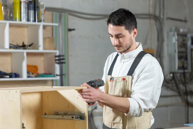 가구 공장, 중소기업 및 사람들 개념-젊은 노동자는 가구 생산을 위해 공장에서 일합니다. 프리미엄 사진