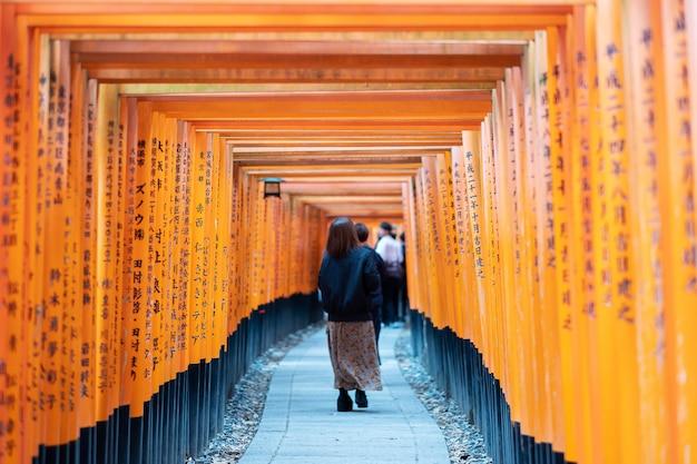 Храм фусими инари-тайша, более 5000 ярких оранжевых ворот тории. это одна из самых популярных святынь в японии. достопримечательности и популярные для туристов достопримечательности в киото. киото Premium Фотографии
