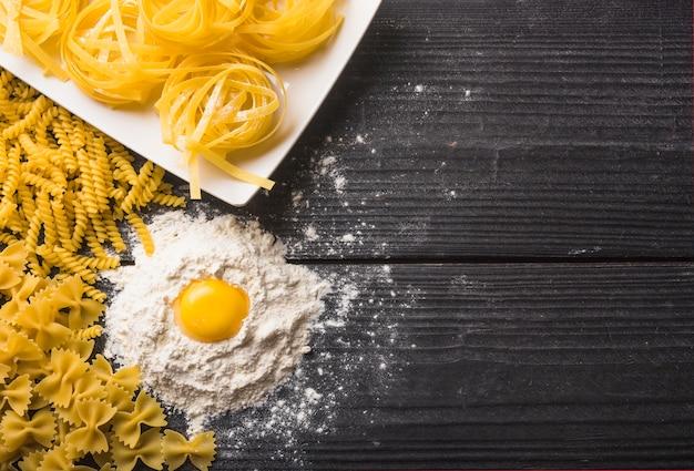 Fusilli; tagliatelle and farfalle pasta with egg yolk on flour Free Photo