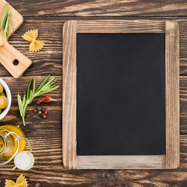Fusilli con olive e verdure accanto alla lavagna Foto Gratuite