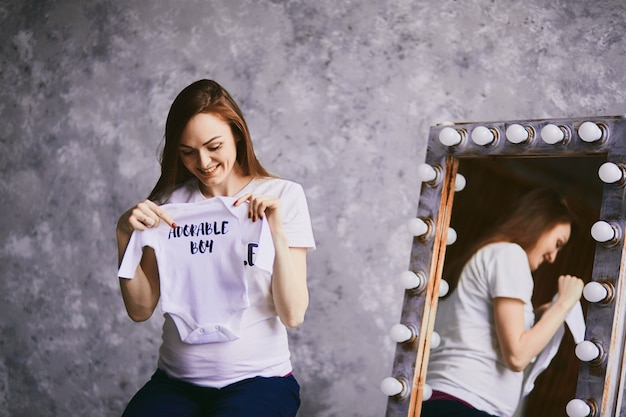 The future mother keeps a shirt for baby Free Photo