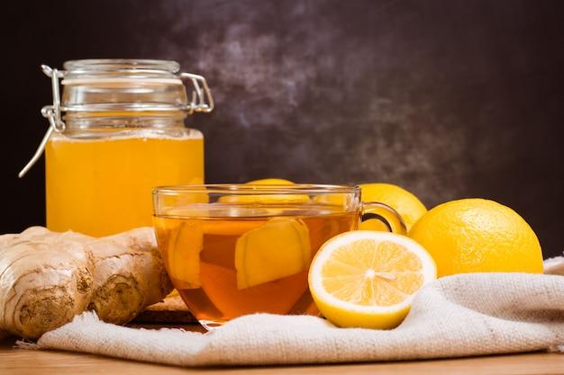 生gとレモンのプレート、蜂蜜の瓶、木製のテーブルの上のレモンと紅茶のカップのスライス Premium写真