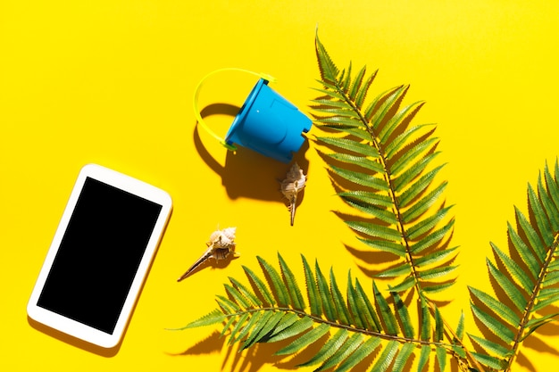 Gadget bucket and palm tree leaf on bright background Free Photo