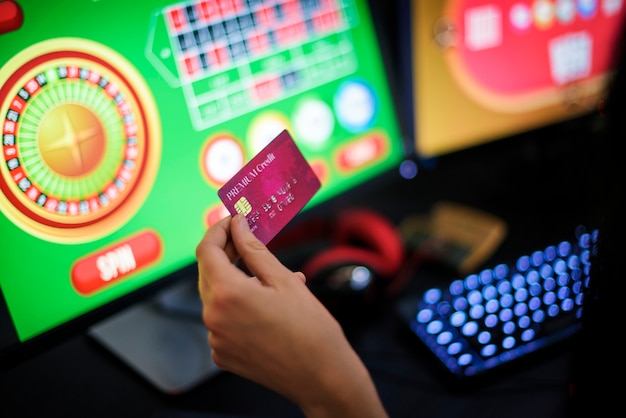 A gambler s hand holding a credit card playing Premium Photo