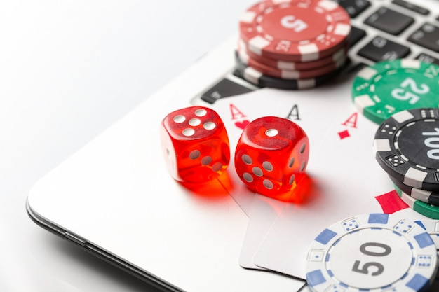 Gambling chips with dice and playing cards on laptop. Premium Photo