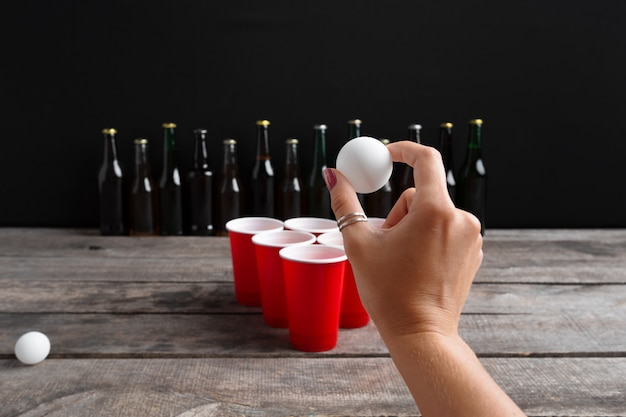 Game beer pong on wooden table Premium Photo