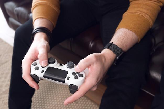 ゲームコンソールゲームでは、男性の手がジョイスティックを持ってゲームコンソールをプレイします。高品質の写真 Premium写真