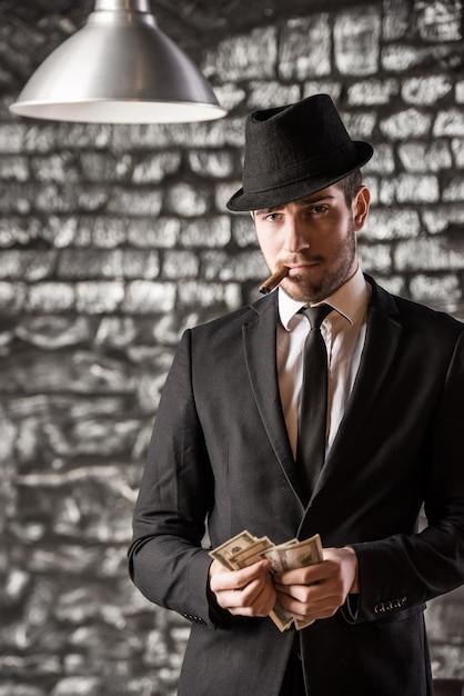 Gangster man is smoking a cuban cigar. Premium Photo
