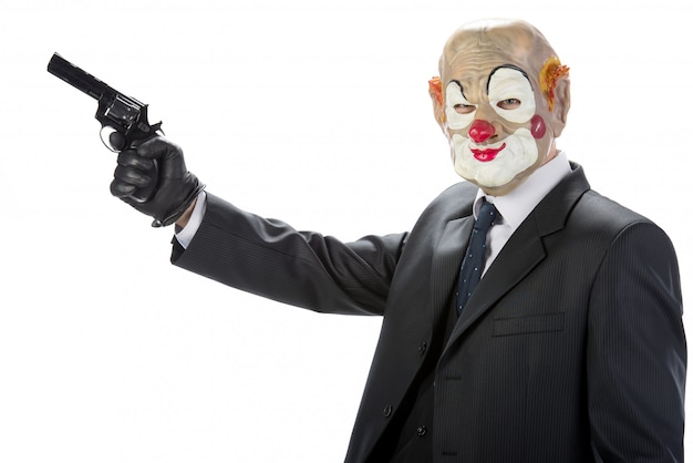 Gangster masked clown with a gun during a robbery. Premium Photo