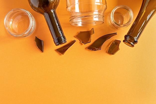 Плоский мусор, стеклянные предметы для повторного использования или переработки лежат на оранжевом фоне с копией пространства Premium Фотографии