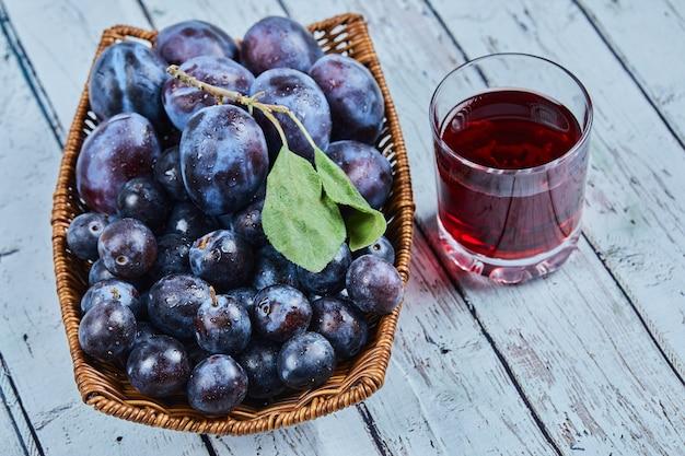 Prugne da giardino in un cestino sull'azzurro con un bicchiere di succo. Foto Gratuite