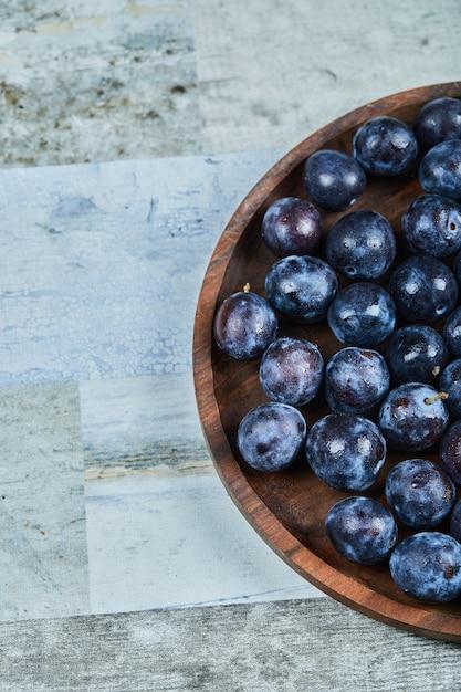 Prugne da giardino in un piatto sull'azzurro. Foto Gratuite