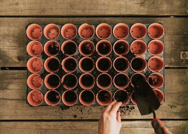 Giardiniere che aggiunge terra ai vasi da fiori flatlay Foto Gratuite