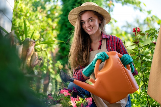 Gardener in hat and apron using watering can for watering flowers in home garden. gardening and floriculture Premium Photo