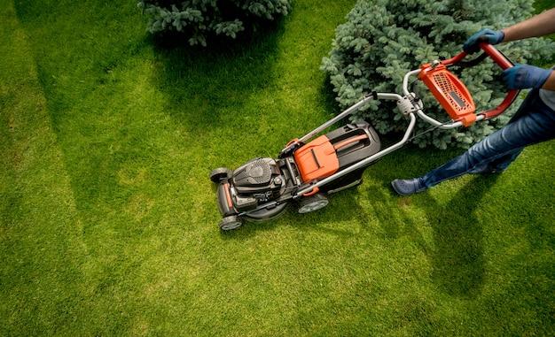 Gardener mowing the lawn. landscape design. green grass background Premium Photo