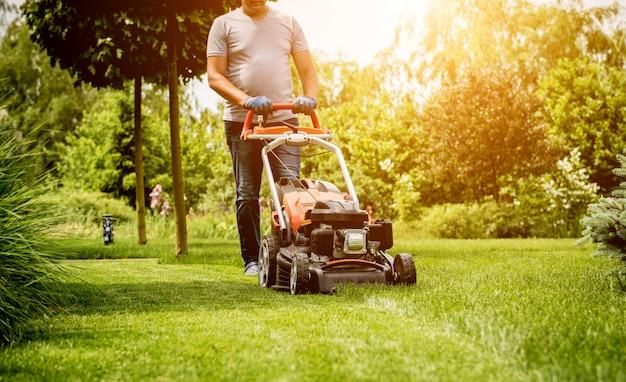 Gardener mowing the lawn. landscape design. Premium Photo