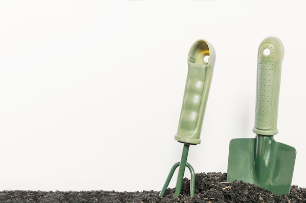 Gardening shovel and gardening rake in plain black soil against isolated on white background Free Photo
