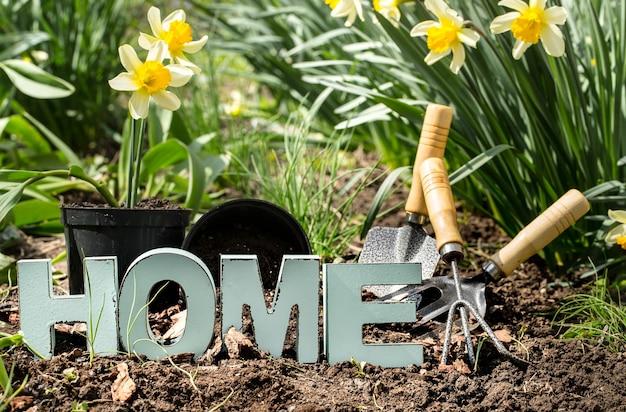 ガーデニング、春の花は庭の供給と黄色い水仙です。土の日。家の碑文と木製の手紙。 無料写真