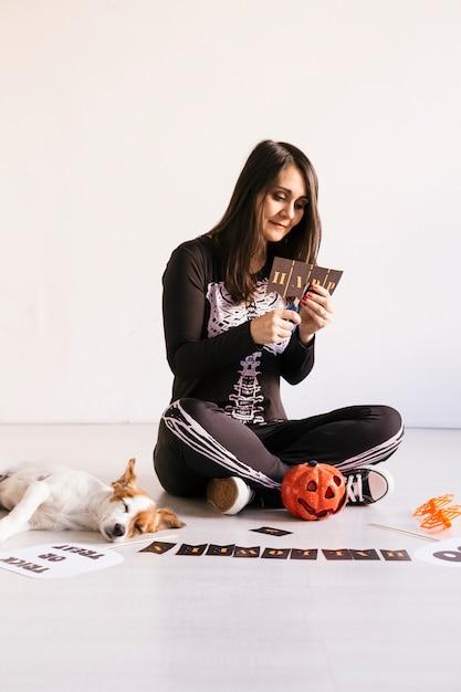 若い女性はハロウィーンgarland.creative diyを作ります。家の装飾プロジェクトパーティー。ハロウィーンクラフトのインスピレーション。キュート小型犬 Premium写真