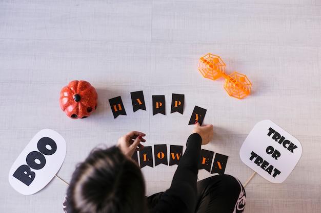若い女性の平面図は、ハロウィーンgarland.creative diyになります。家の装飾プロジェクトパーティー。ハロウィーンクラフトのインスピレーション。 Premium写真