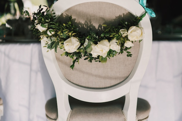Garland of beautiful white roses hangs on the back of grey chair Free Photo