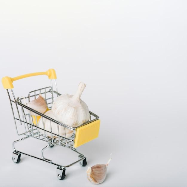 Garlic bulbs in shopping cart on white backdrop Free Photo