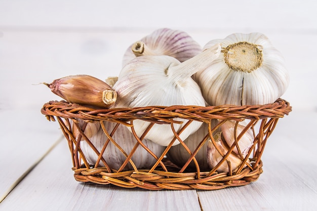 Garlic cloves and garlic bulb in a basket on a white wooden table. Premium Photo