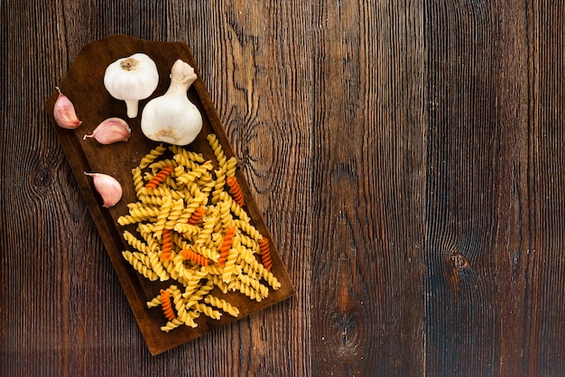 Garlic and fusilli pasta on cutting board over wooden textured background Free Photo