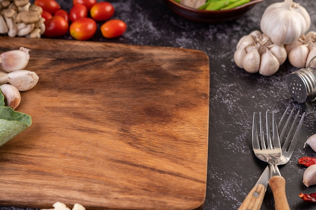 Garlic, tomato, cutting board, and cooking fork. Free Photo
